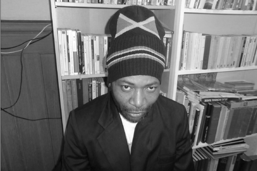 Wesley boasting his Jamaican flag beanie while sitting in Espace Solidaire Paquis library (Photography : Delphine Luchetta)